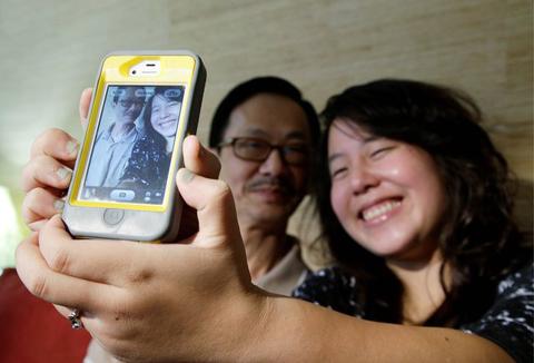 Viola Van, một sinh viên của dự án Trải nghiệm người Mỹ gốc Việt, đang chụp hình cùng bố của cô, ông Hugo. Ảnh: AP