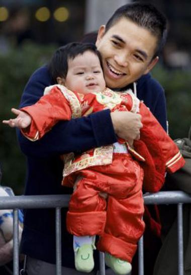 Anthony Dang, một người Mỹ gốc Việt, cùng cậu con trai 9 tháng tuổi theo dõi lễ diễu hành tại thành phố Westminster.