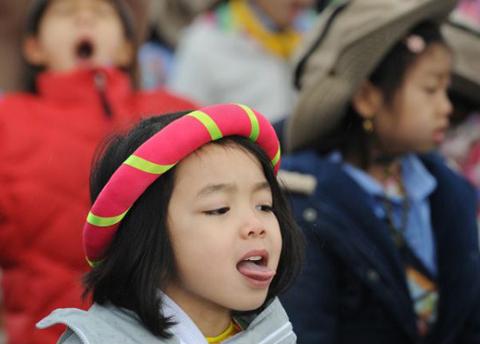 Thien Ai, 5 tuổi, thè lưỡi để hứng những giọt nước mưa khi cô bé chuẩn bị diễu hành mừng Tết tại thành phố Westminster, quận Cam, bang California, Mỹ hôm 10/2.