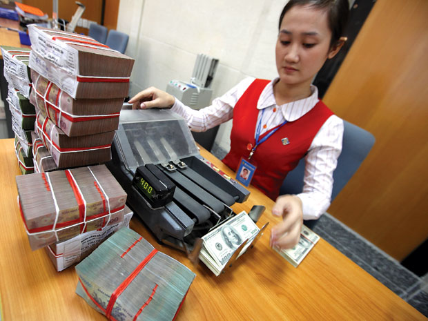 Việc chuyển USD sang VND để gửi tiết kiệm vẫn đang diễn ra. Ảnh: Lê Quang Nhật